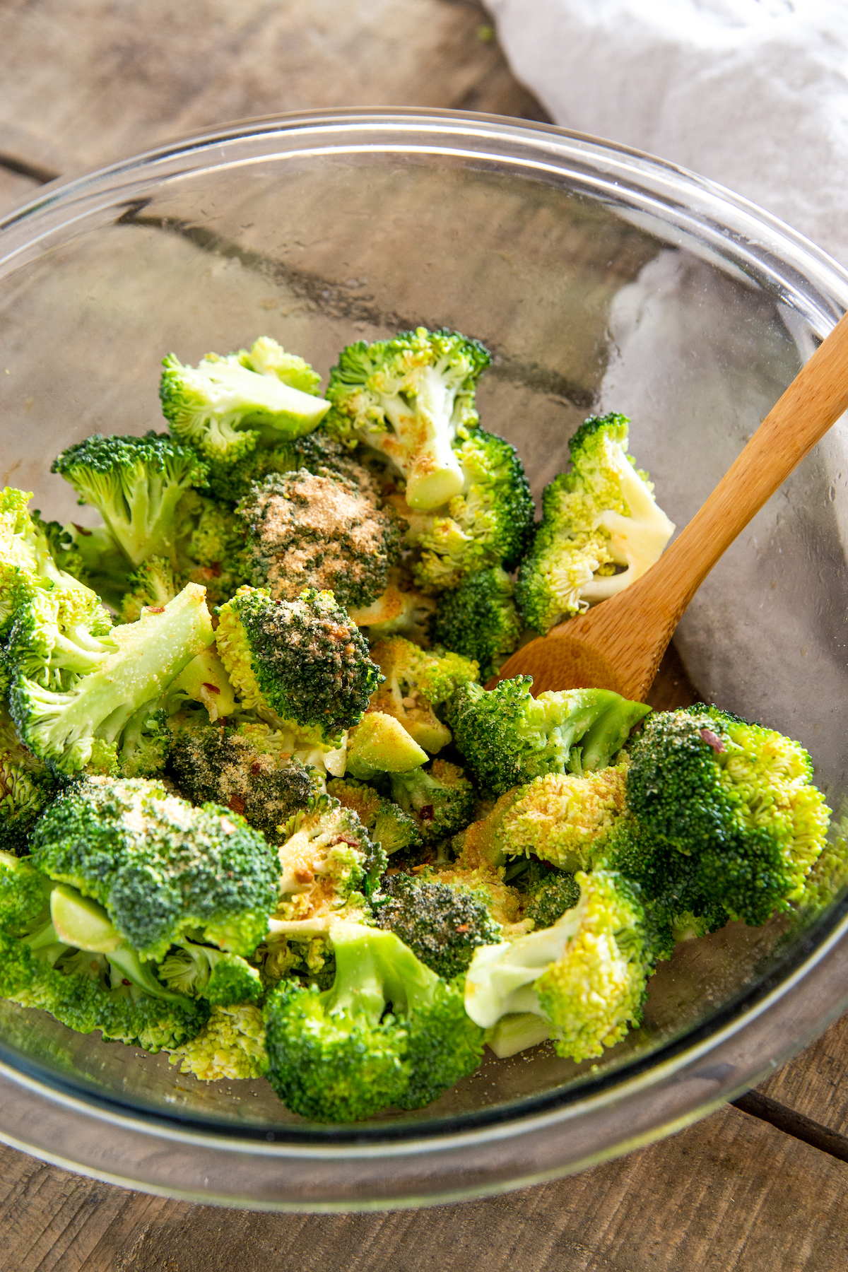 Seasoned broccoli florets in a bowl.