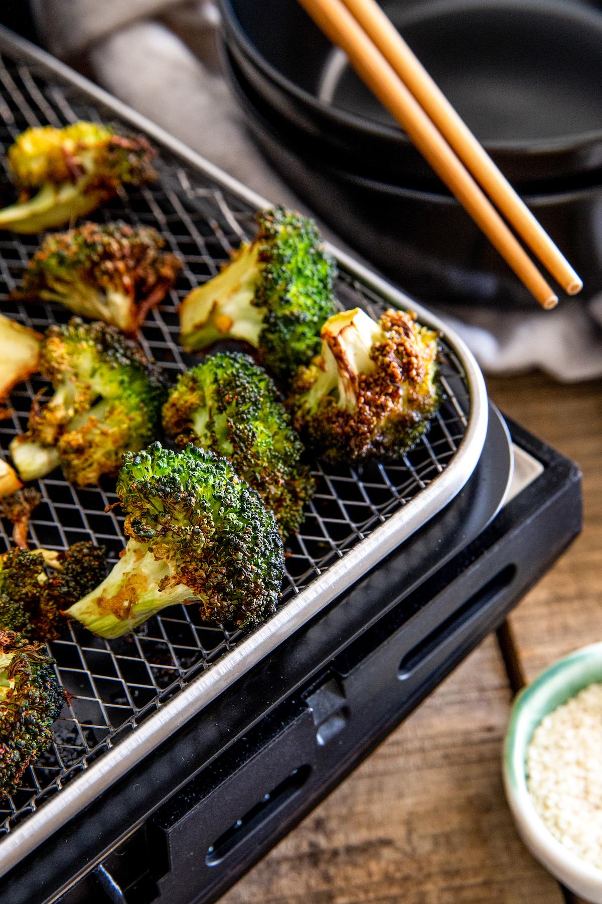 Roasted broccoli on an air fryer tray.