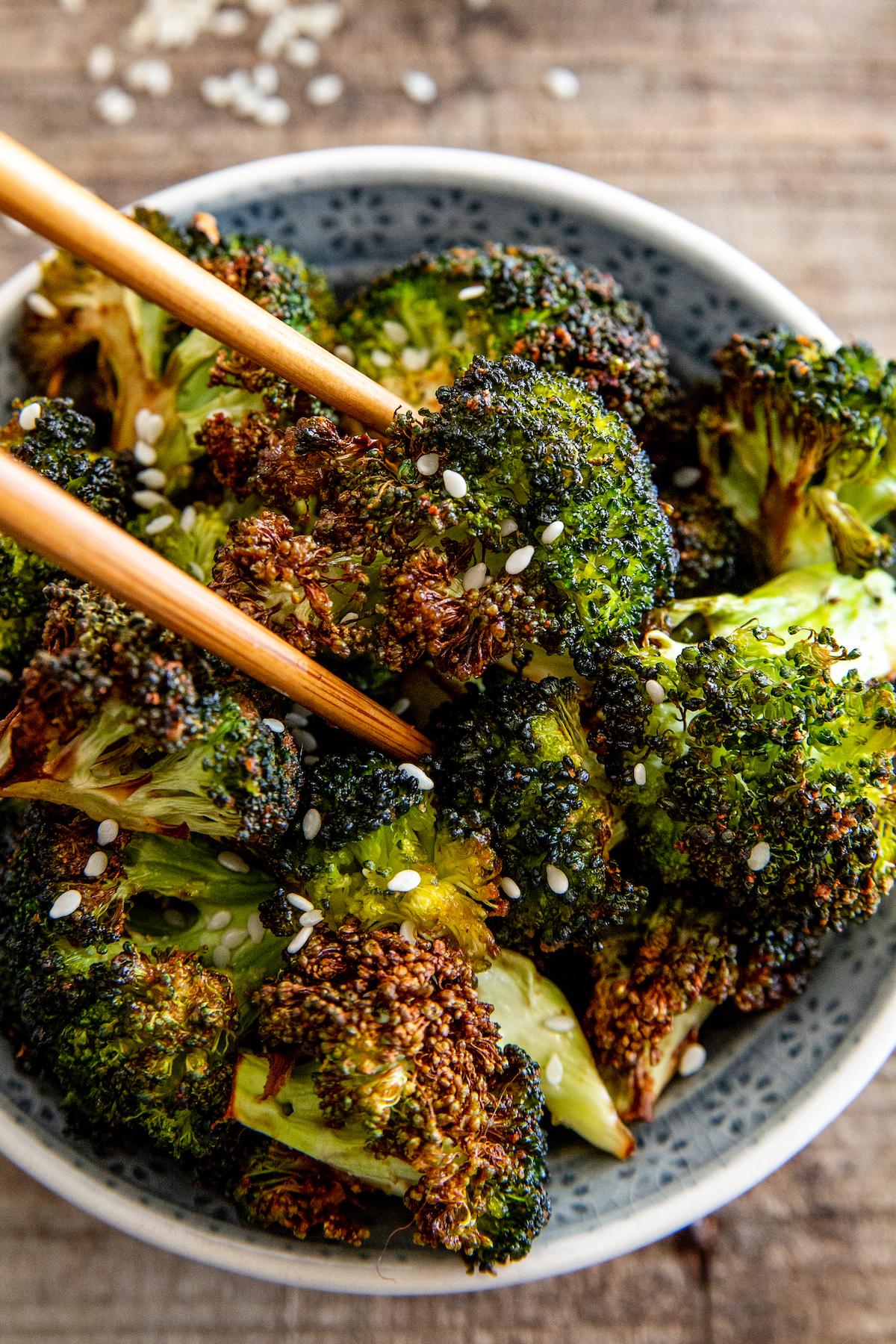 Roasted broccoli in chopsticks.