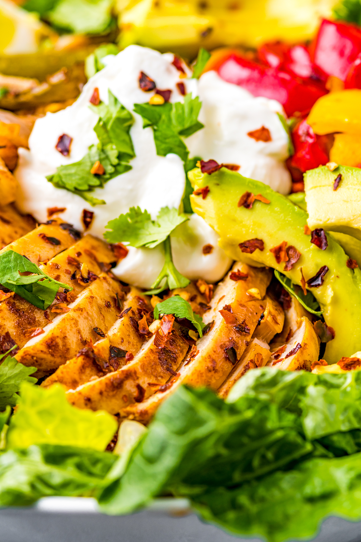 Chicken fajita salad with sour cream.