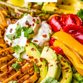 Image of chicken fajita salad in a bowl with avocado and sour cream on top.