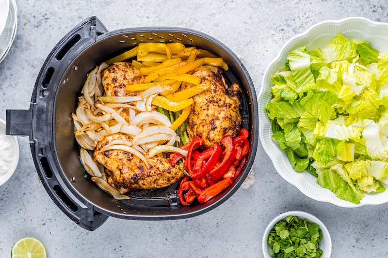 Overhead image of an air fryer basket with roasted vegetables placed on top of chicken breasts and a bowl of romaine lettuce on the side.