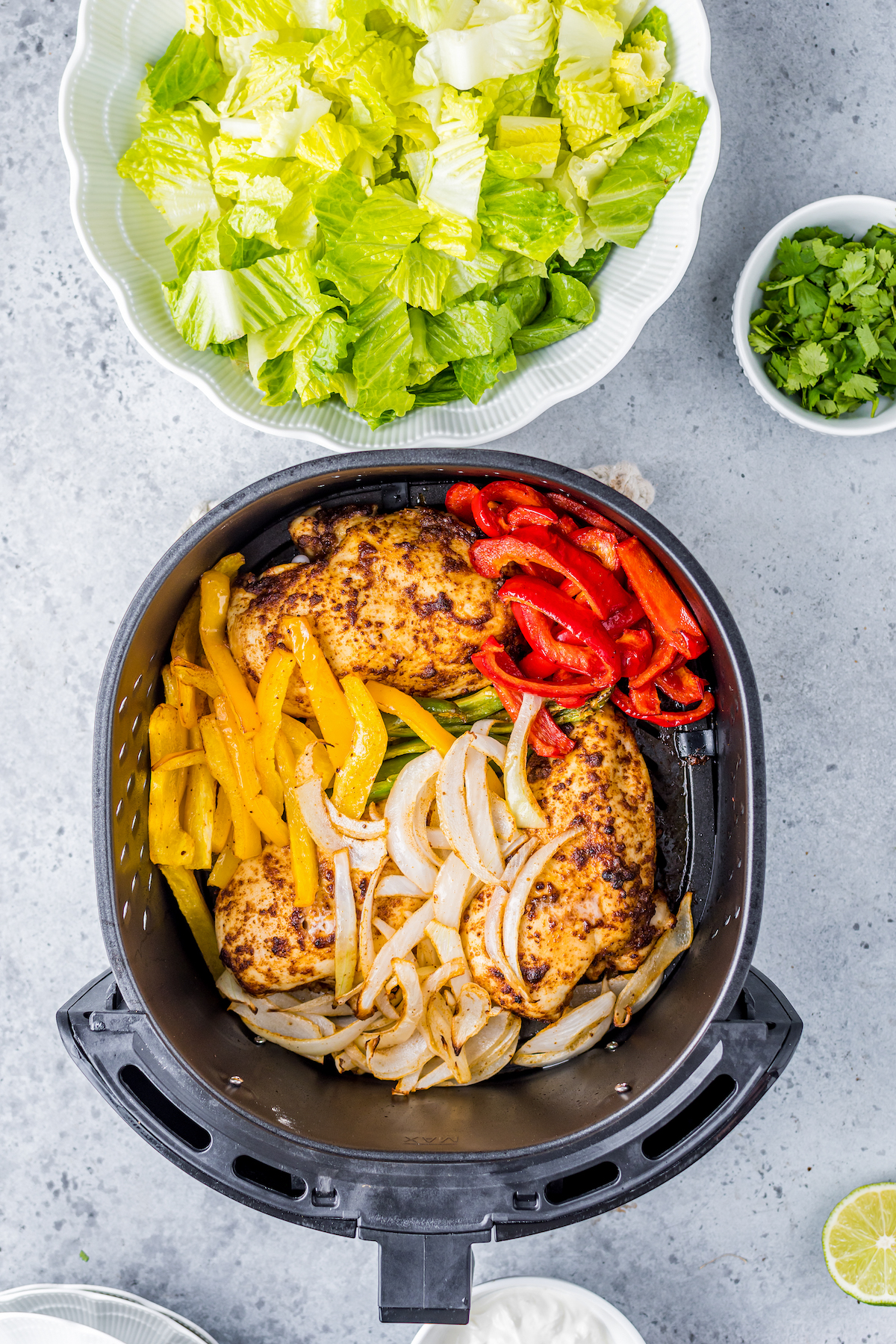 Air fryer with chicken and vegetables in it.