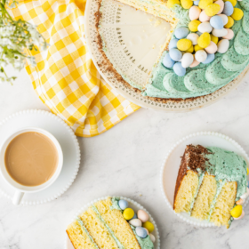 Overhead of easter cake on a cake plate with a yellow napkin and two slices of cake on plates.