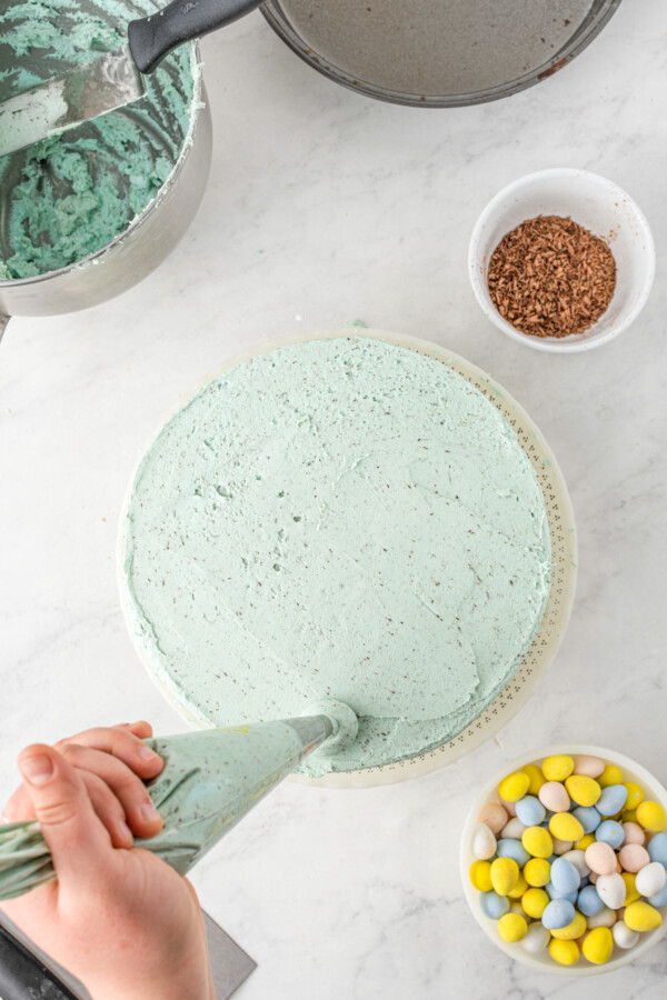 Frosting being piped onto the edge of a cake.