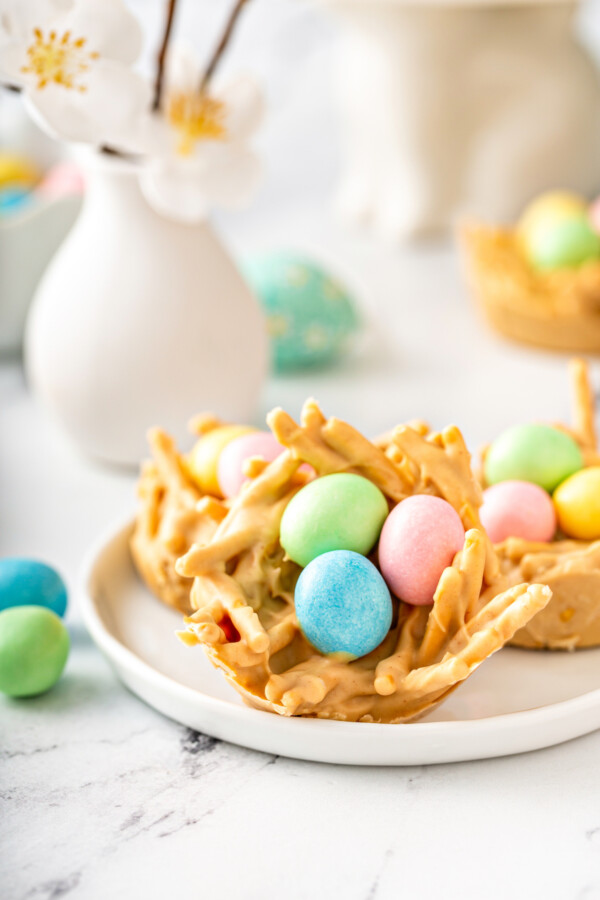 A haystack is topped with pink, green, and blue eggs.