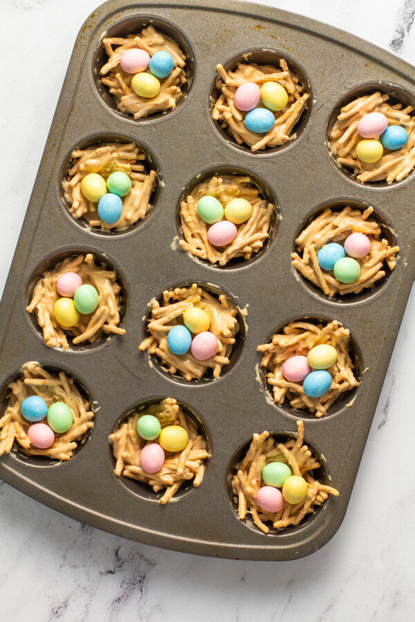 Pastel candy eggs are placed in the middles of the haystacks.