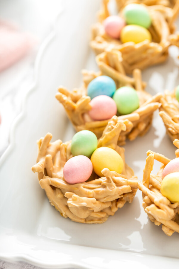 Haystacks are topped with pink, green, and blue eggs on a white plate.
