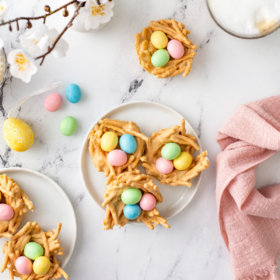 Overhead view of easter haystacks on a white marble background with white plate sand a pink napkin.
