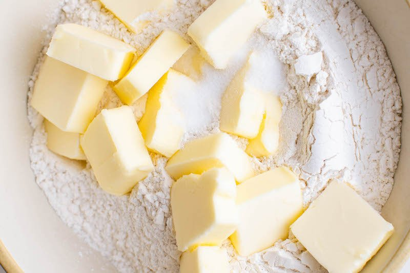 Cubed butter sitting on top of flour in a bowl.