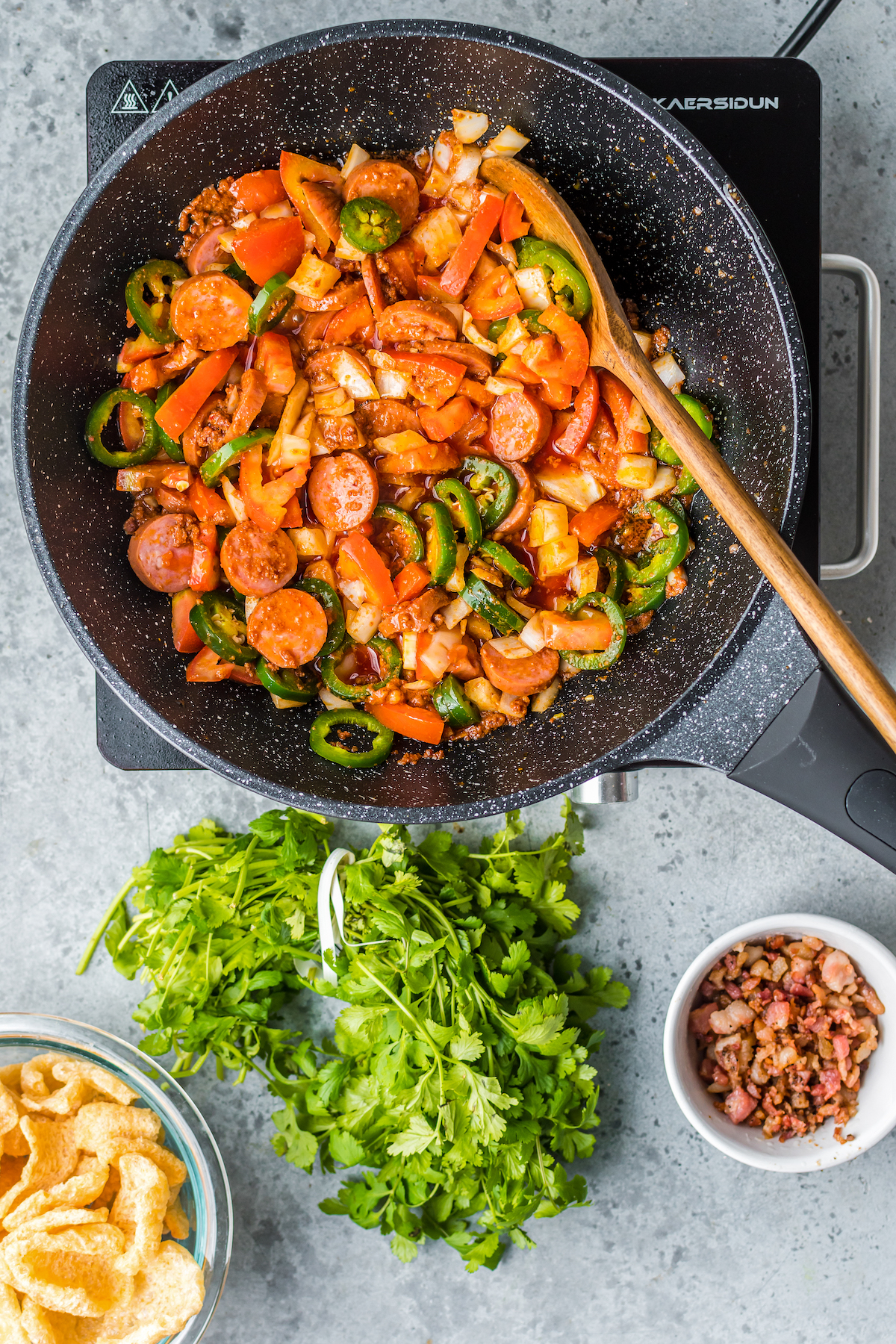 Sausage and vegetables being sautéed in a pan.