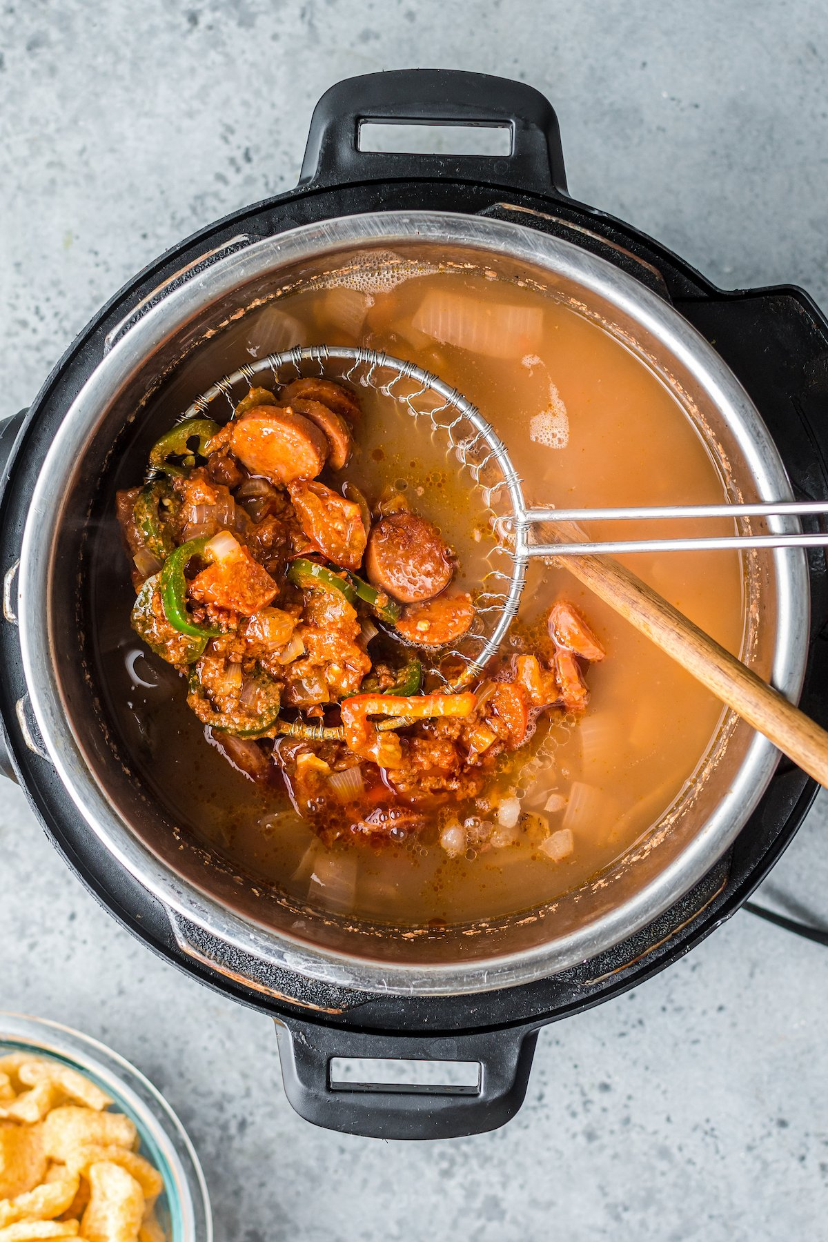 Sausage and vegetables in a strainer.