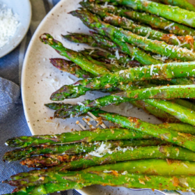 Overhead view of cooked asparagus on a white plate with parmesan and lemon wedges.