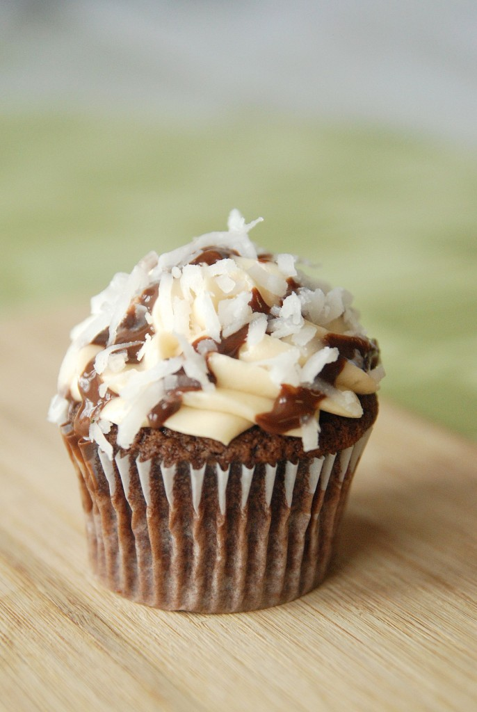 A Single Samoas Cupcake with Flaked Coconut, Homemade Chocolate Sauce and Caramel Frosting on Top