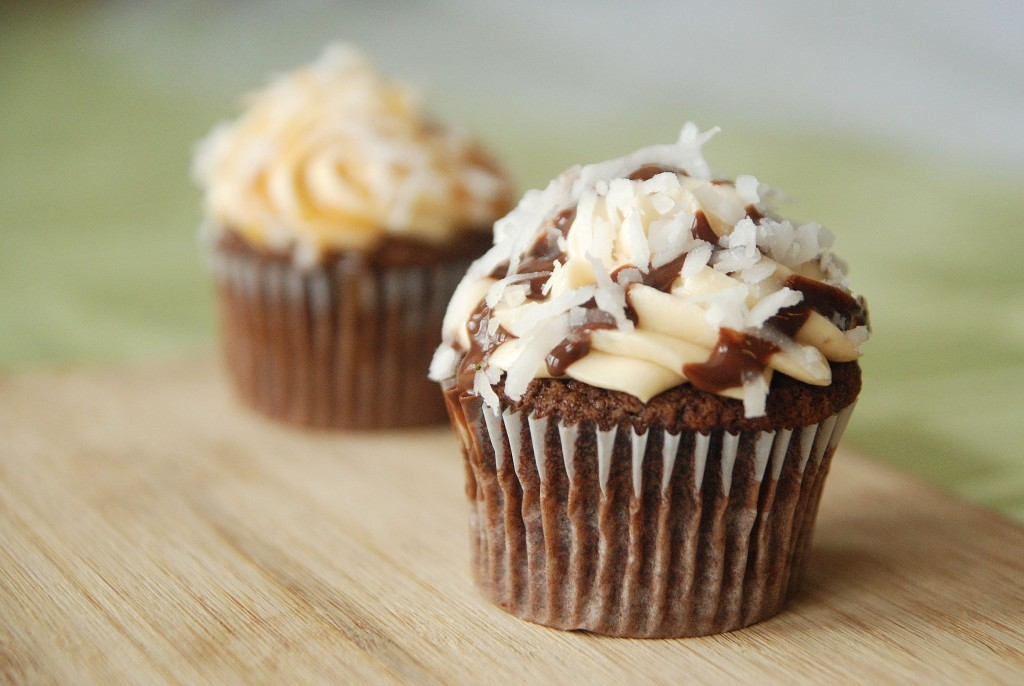 A Samoas Cupcake Topped with Buttercream, Chocolate Sauce and Coconut Flakes