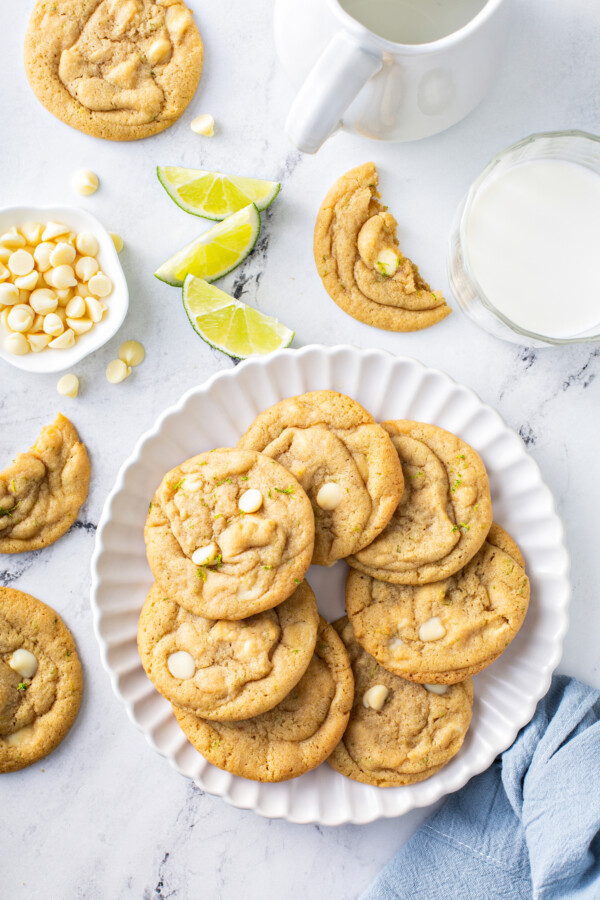 A plate filled with White Chocolate Key Lime Cookies is placed next to several other cookies on a white surface.