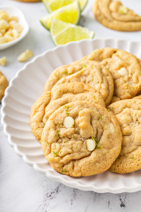 A plate of white chocolate chip cookies is placed on a marble counter.
