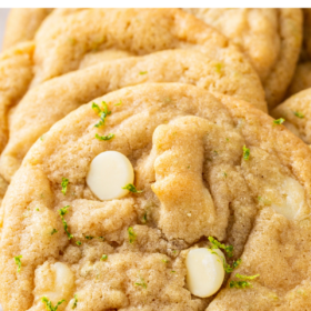 A close up shot shows white chocolate chips baked into zested cookie dough.