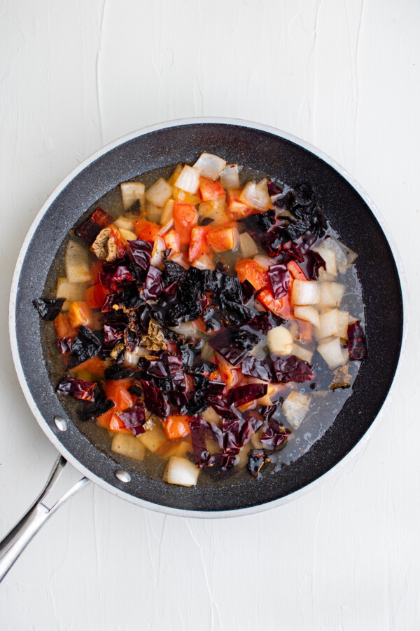 Sautéed vegetables with chicken broth in a pan.
