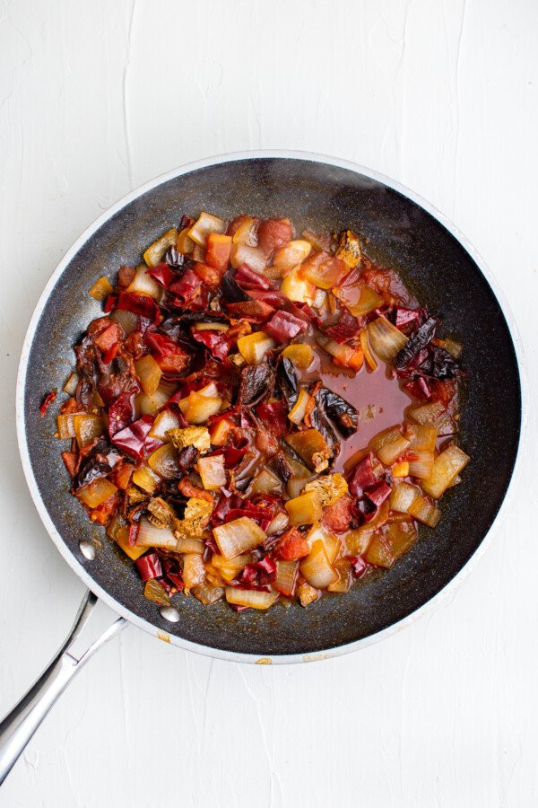 Chiles and sautéed vegetables in a pan.