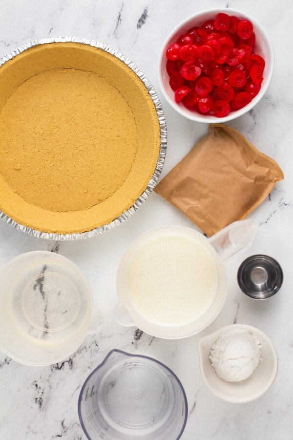 Ingredients for a cherry pie in bowls on a marble counter top.