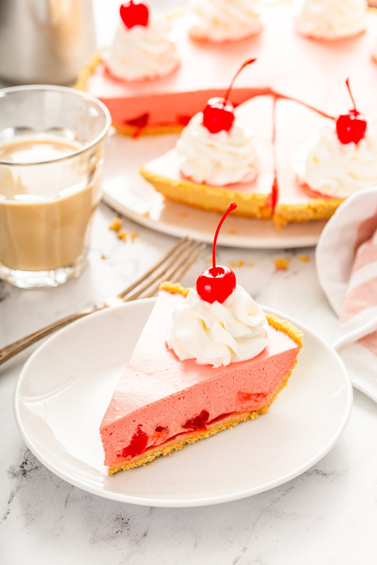 A slice of cherry jello pie on a white plate with the full pie behind it in the background.