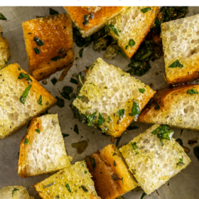 Up close image of croutons on a sheet pan with parchment paper.
