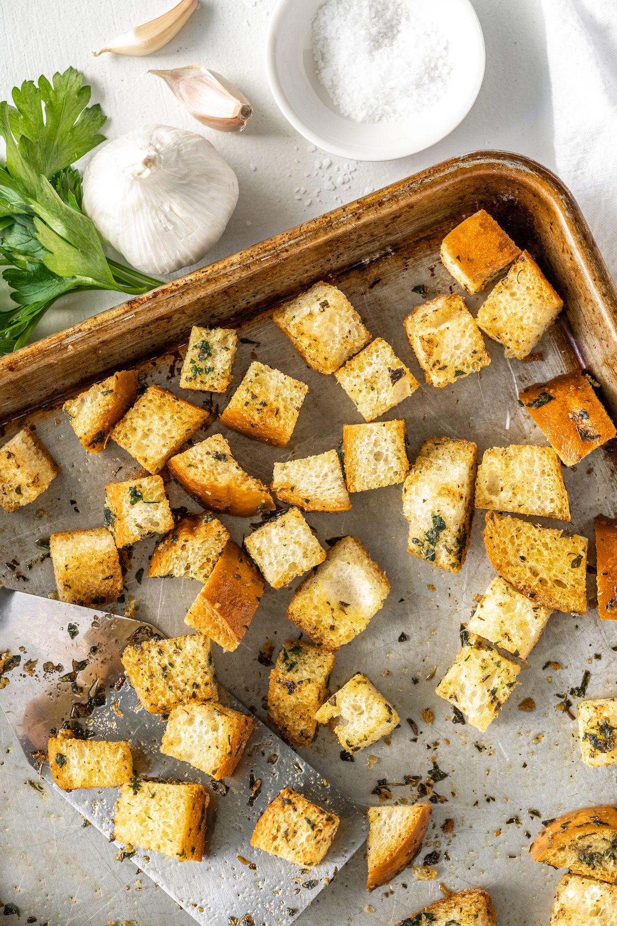 Baked homemade croutons on a baking pan.