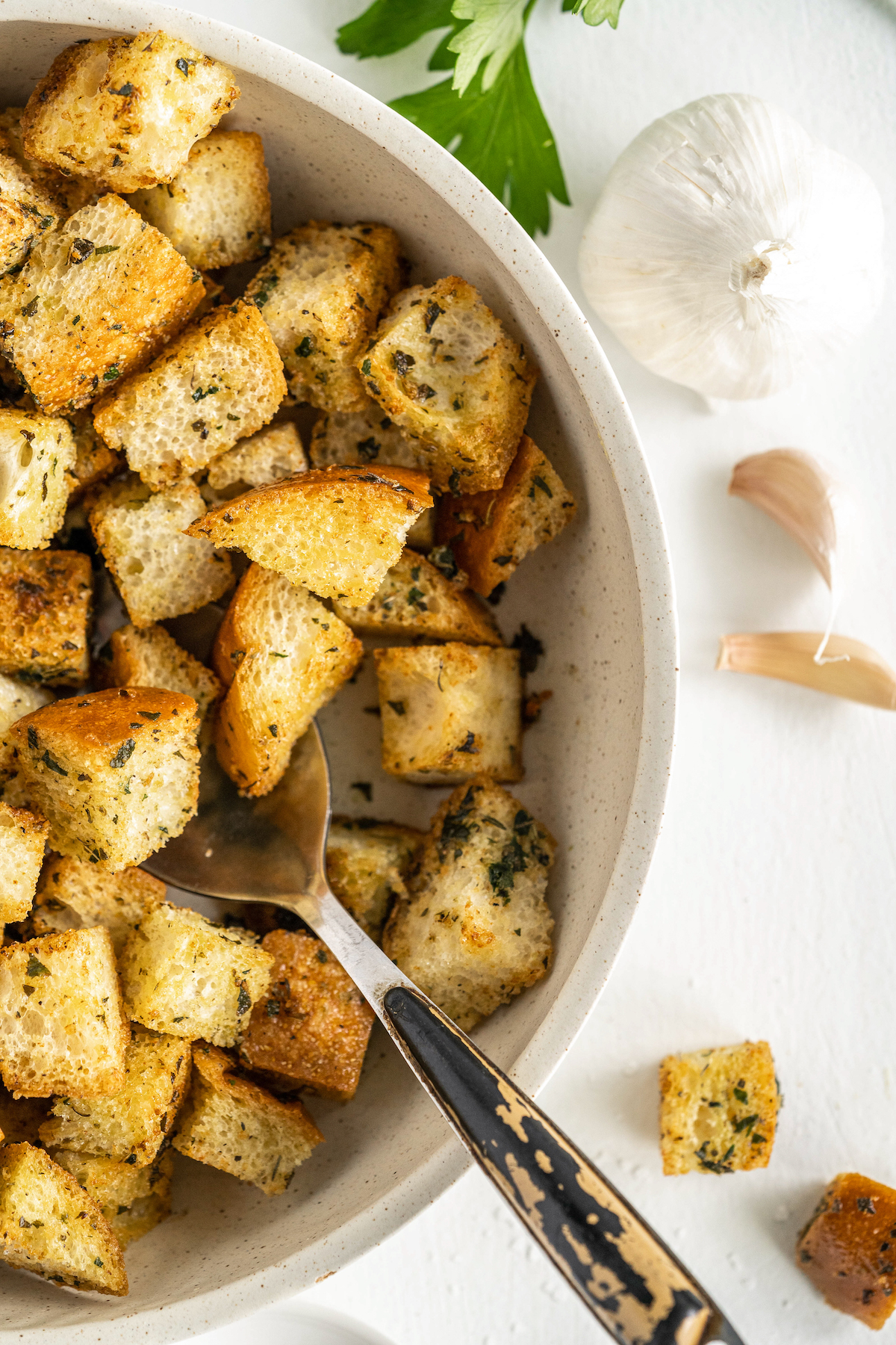 Bowl of crunchy homemade croutons with a spoon.