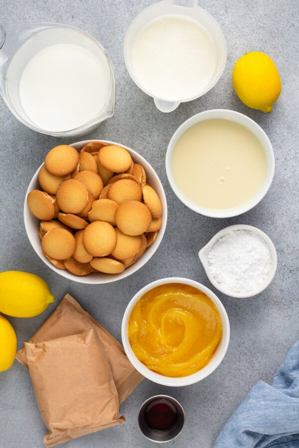 Ingredients for lemon pudding in white bowls.