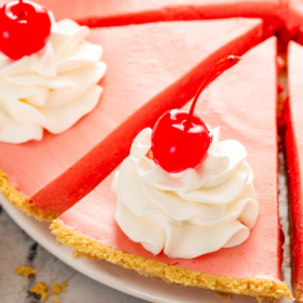 Overhead image of cherry pie sliced into pieces with whip cream and cherries on top.