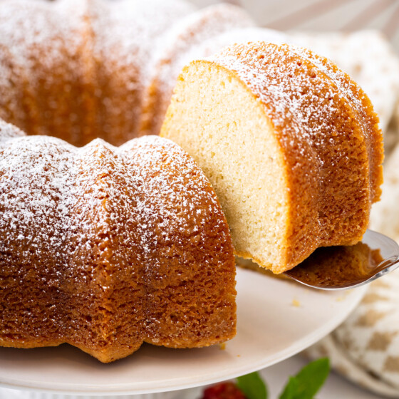 A slice of vanilla bean pound cake on a cake stand with powdered sugar on top.