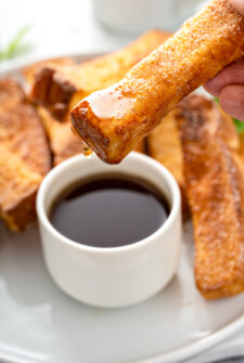 A French toast stick is being dipped into a small cup of syrup.