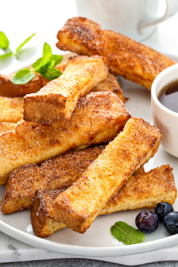 A stack of French toast sticks is on a white plate.
