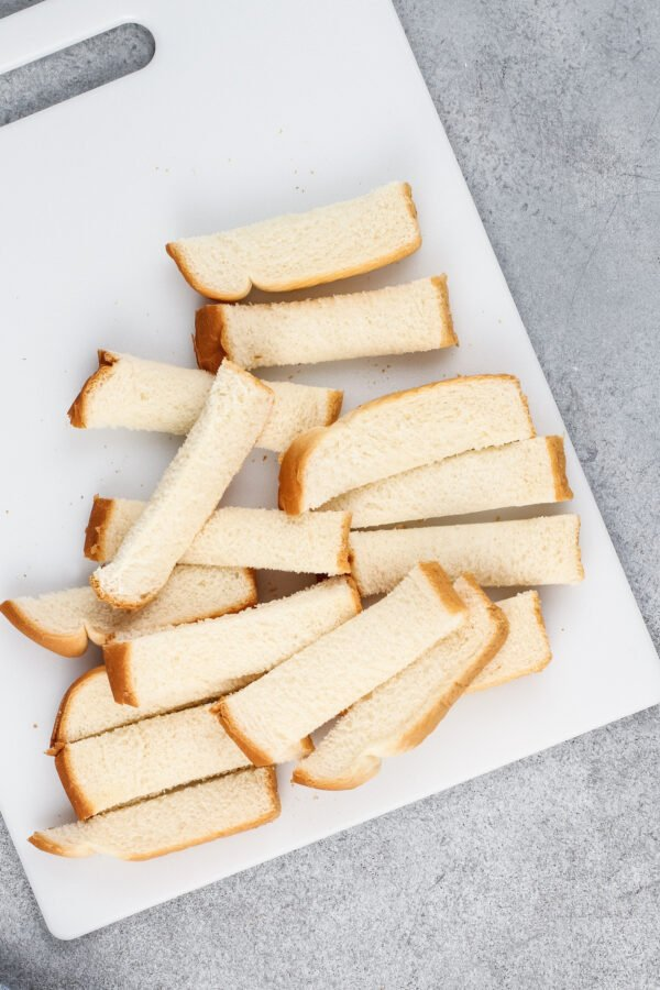 Sliced white bread is placed on a cutting board.