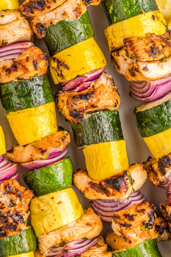 Chicken kabobs with zucchini, yellow squash, and red onions.