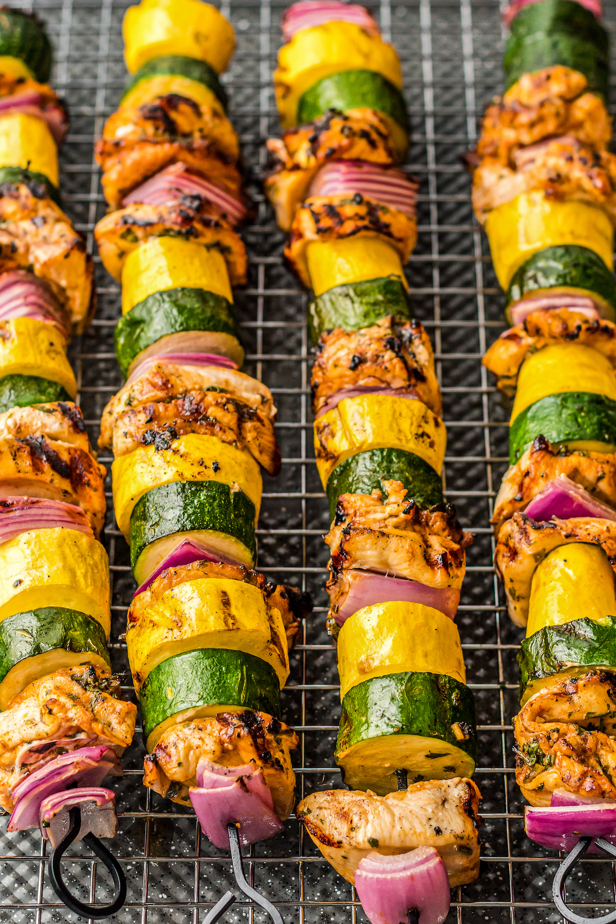 Grilled chicken shish kabobs on a cooling rack.