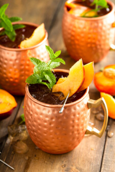 Three copper mugs are filled with peach Moscow mules.