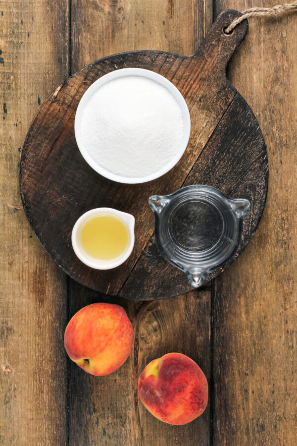 The ingredients for peach simple syrup are placed on a wooden surface.
