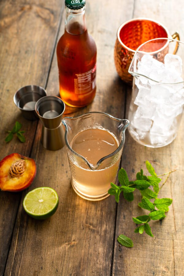 The ingredients for a Moscow Mule are placed on a wooden table.