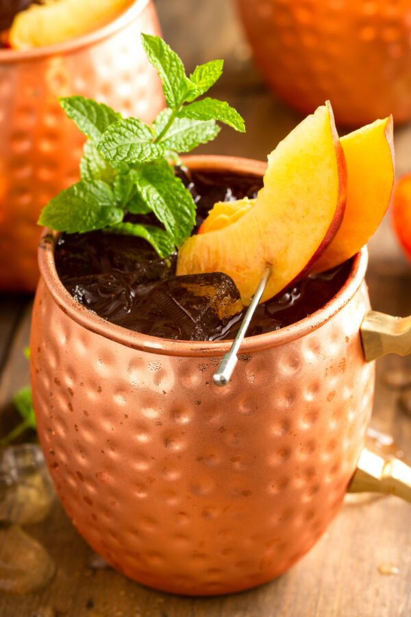 Peaches and mint sprigs garnish a copper mug filled with fruity Moscow Mule.