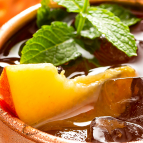 Up close image of a peach Moscow Mule with a peach and a piece of mint on top.