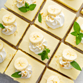 Banana pudding bars are garnished with banana slices, whipped cream and mint sprigs.