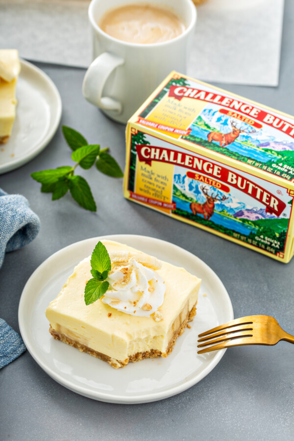 A fork is placed on a white plate with a bar of banana pudding next to a box of challenge butter.
