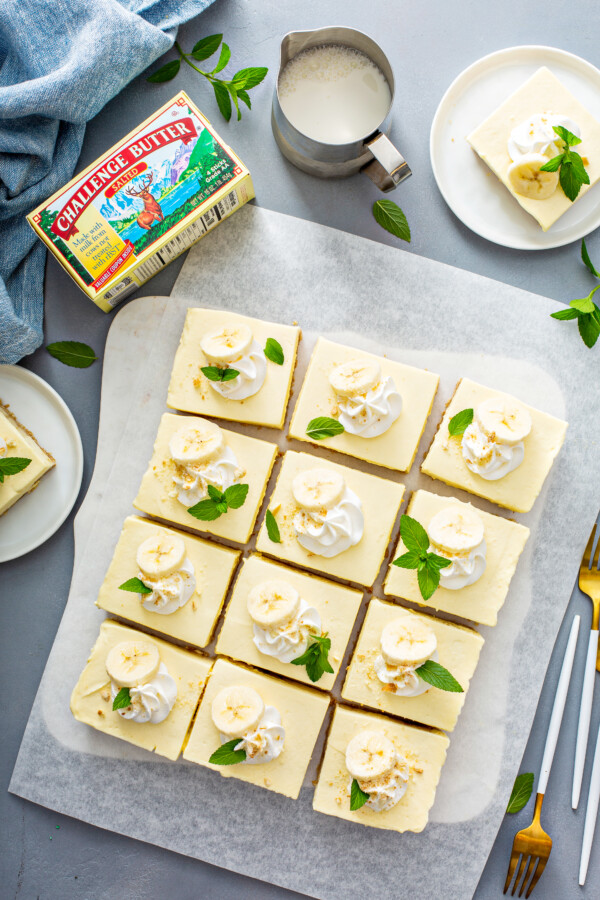 Overhead image of Banana pudding bars are garnished with banana slices, whipped cream and mint sprigs.
