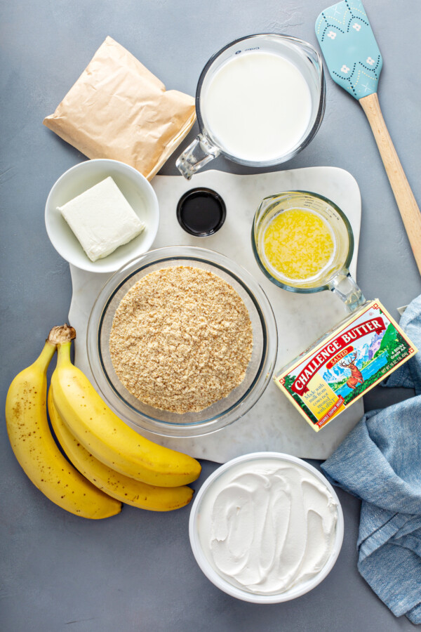The ingredients for banana pudding bars are spread out on a gray surface.