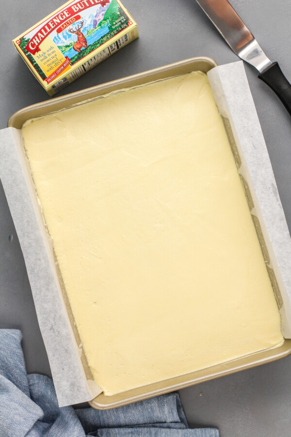 Pudding is spread in an even layer in a baking sheet.