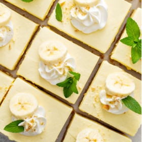 Overhead image of banana pudding bars with mint, whipped cream and banana slices on top.