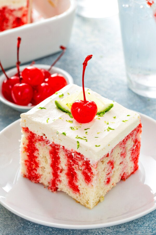 A slice of cherry limeade cake on a white plate with lime and a cherry on top.