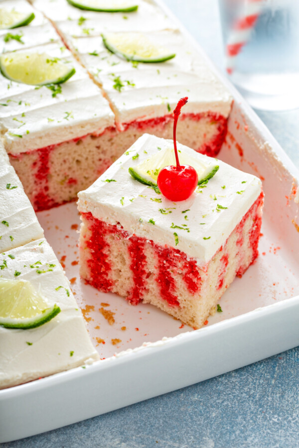 A slice of cherry limeade poke cake in the baking pan with lime zest and a cherry on top.